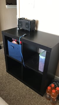 Black wooden table with 4 holes for cubbies