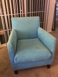 blue fabric sofa chair with throw pillow