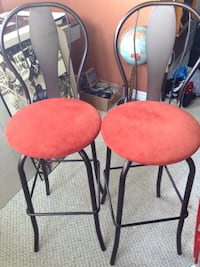 two black metal framed red suede seat bar stools