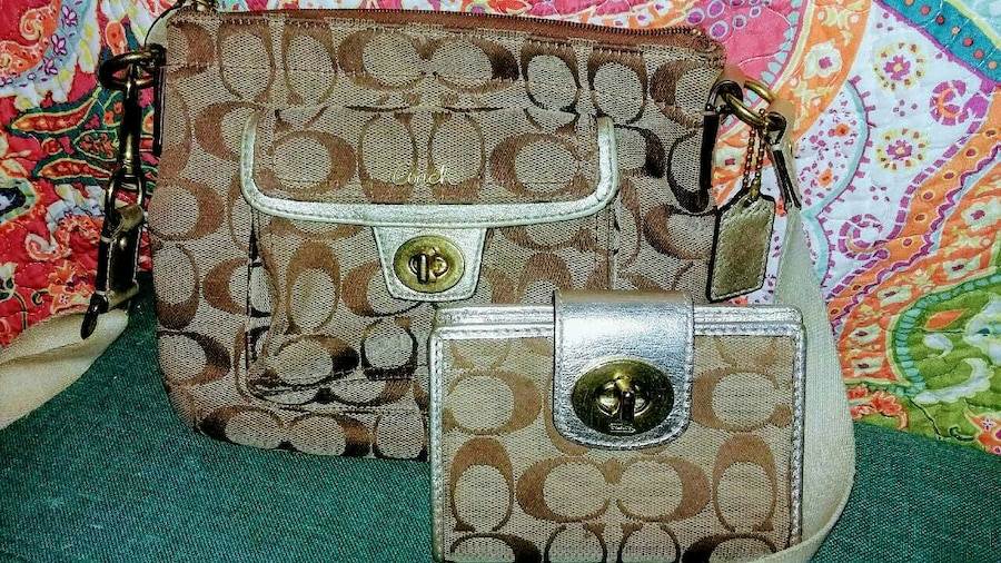 two brown-and-white Coach handbags
