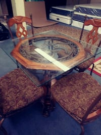 square glass top table with brown wooden base and four chairs dining set Providence, 02904