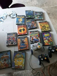 two black and one white Nintendo Game Cube game controllers and assorted game cases Sarnia, N7T 4M4