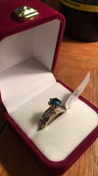 gold-colored blue gemstone ring with red case