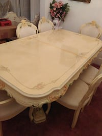 Italian-style cream color dining table with six matching chairs.