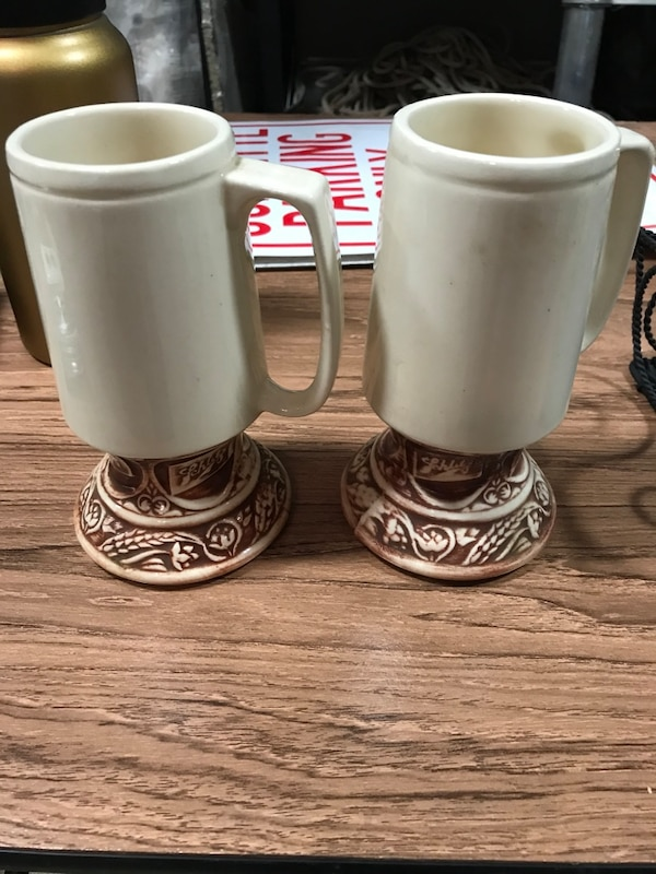 Two white ceramic Schlitz beer mugs