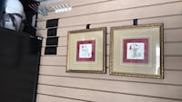 two brass-colored framed paintings