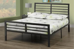 Black metal bed with covered mattress