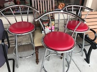 three stainless steel bar chairs