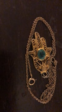 Hamas hand with green stone on goldtone chain New York, 10021