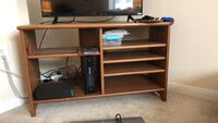 Black flat screen tv; brown wooden tv stand