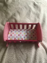 pink and white doll cradle