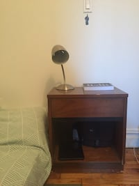 brown wooden single-drawer night stand and gray desk lamp