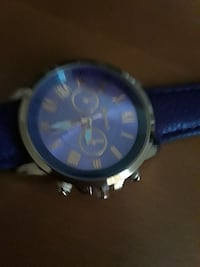 round silver chronograph watch with blue leather s