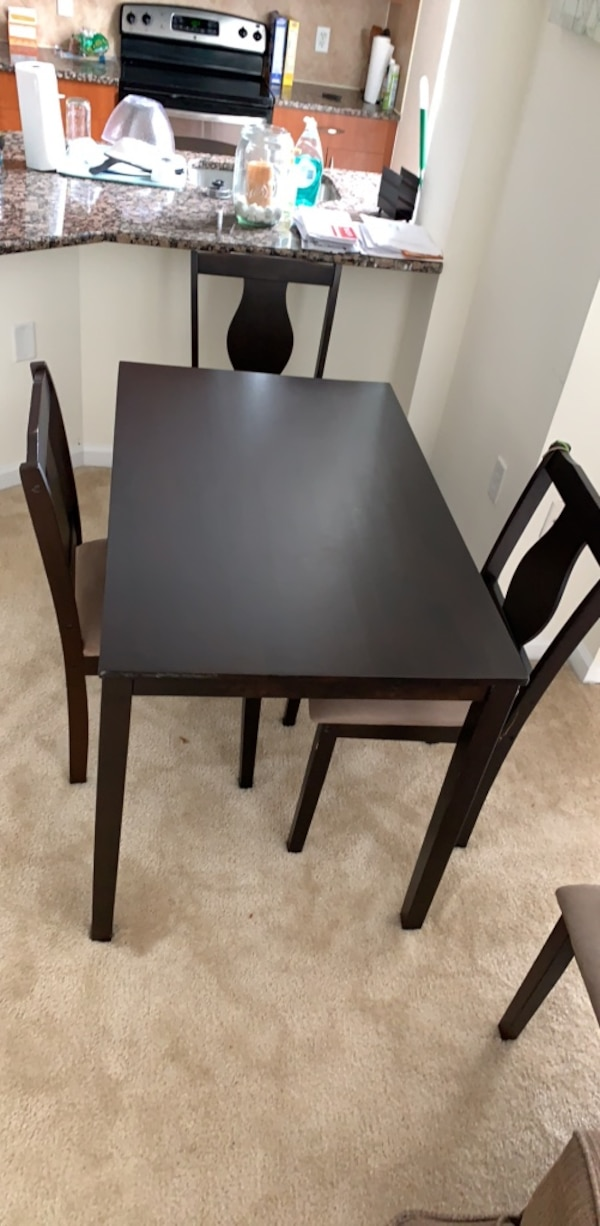 Rectangular black wooden table with three chairs dining set