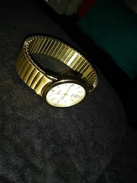 round gold timex watch with gold link bracelet