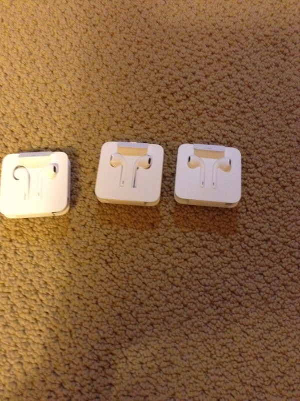 Three white IPONE ear pods