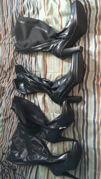 Pair of black leather heeled boots one pair left on the right