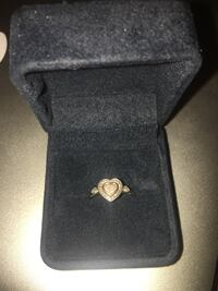 Gold-colored ring with heart gemstone and box