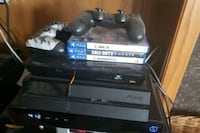 black Sony PS4 console with controller and game cases Calgary, T2Z 2K4
