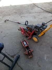yellow and red lawn edger, red string trimmer and red floor jack
