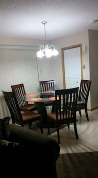 Round brown wooden table with five chairs din Calgary, T2Y 3T5