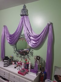 purple curtain with round frame wall mirror