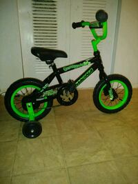 toddler's black and green bicycle with training wh