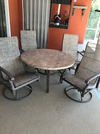 """Round 48"""" brown Winston table with four swivel recliner chairs Fort Myers, 33908"""