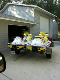 two white-and-yellow personal watercraft