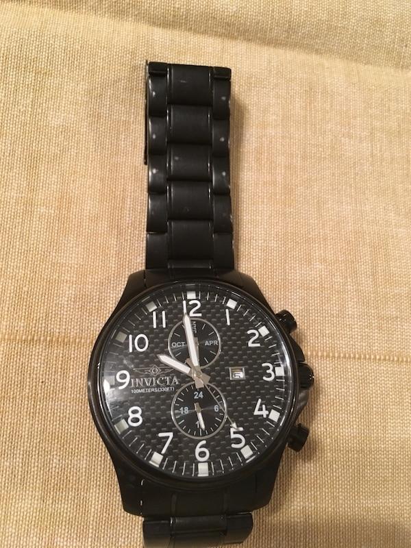 Round black face invicta chronograph watch with black strap