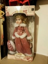 Porcelain Doll in pink velvet outfit.  Has certificate of authenticity