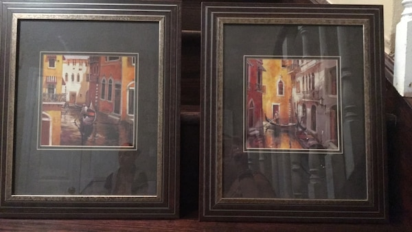 two village paintings with brown wooden frames