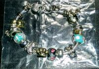 silver-colored and green gemstone encrusted bracelet 21 mi