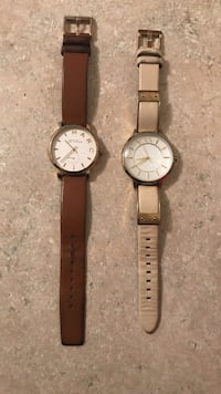 two round gold-colored analog watches with brown and beige leather straps