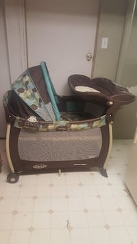 baby's black and green Graco pack n play