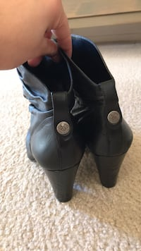 pair of black leather cone heel boots