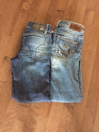 two pairs of washed blue denim bottoms