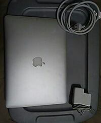 silver Apple laptop with adapter