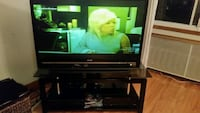 black flat screen TV with brown wooden TV stand Montréal, H8N 1E4