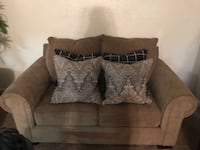 brown fabric loveseat with four throw pillows