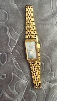 Square gold analog watch with gold link bracelet