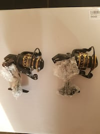 two black-and-gold fishing reels