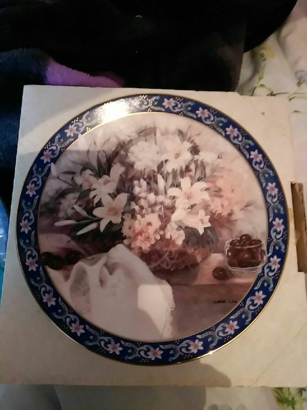 round blue-framed painting of white flowers