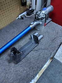 blue and gray Dyson stick vacuum cleaner
