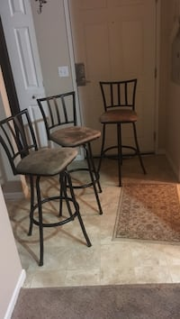 Three black metal framed brown padded chairs