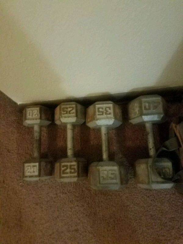 four gray fixed weight dumbbells