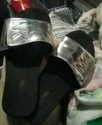 pair of black-and-gray MK slide-on sandals