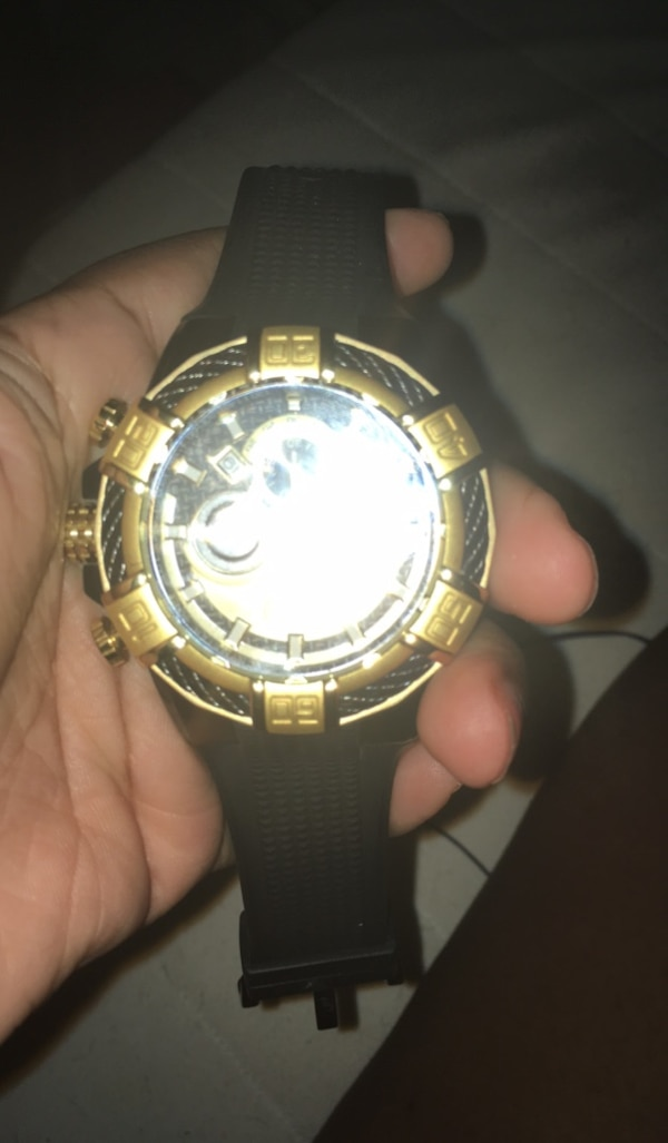 Round gold-colored analog watch with black strap
