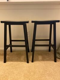 Two black wood stools