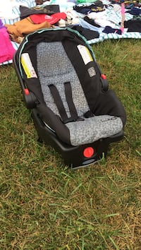Baby's gray and black polka-dot car seat carrier with base